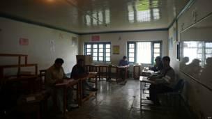 श्रीनगर के एक मतदान केंद्र पर मतदाताओं के इंतज़ार में बैठे चुनाव अधिकारी.