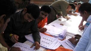 पंजाब के अमृतसर में एक राजनीतिक दल के बूथ पर मतदाता सूची में अपना नाम खोजते मतदाता.