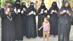 रायबरेली में मतदान के बाद अपनी उंगलियां और मतदाता पहचान पत्र दिखाती मुसलमान महिलाएं.