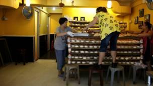 एक बेकरी के अंदर बन महोत्सव के लिए बन बनाते मज़दूर.