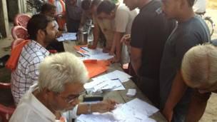 फ़ैज़ाबाद के एक मतदान केंद्र के बाहर एक बूथ पर मतदाता सूची में अपना नाम खोजते मतदाता.