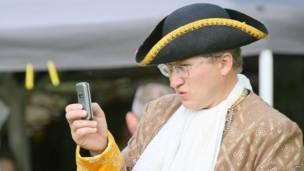 Мужчина в старинном костюме с мобильным в руке