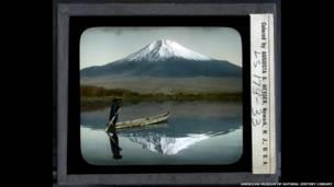 जापान का फूजी पर्वत और नाव चलाता एक व्यक्ति.