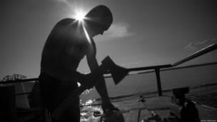 Мужчина разделывает рыбу топором