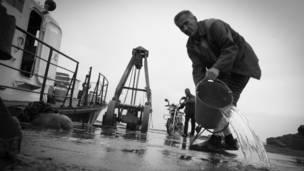 Мужчина выливает воду из ведра на палубу
