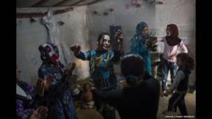 شامی مہاجرین کے کیمپ میں ہونے والی ایک شادی تقریب میں ایک مہاجر خاتون رقص کر رہی ہے