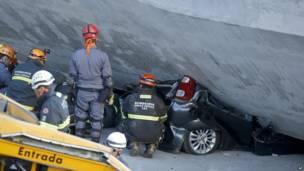 سيارة تحت أنقاض الجسر ورجال الإنقاذ يحاولون استخراجها