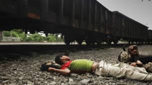Migrantes tomando un descanso cerca del ferrocarril