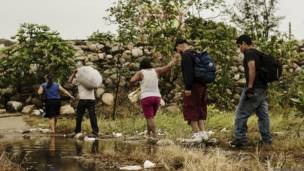 Migrantes cruzan una cañada