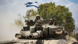 En la imagen, un soldado israelí saluda mientras conduce un tanque Merkava en la frontera con Gaza. Crédito: AFP/Getty.