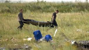 Dos rescatistas llevan el cadáver de una víctima