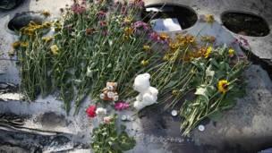 Flores y recuerdos sobre los restos del avión