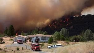 """Un equipo de bomberos protege una casa evacuada en las cercanías de Plymouth, California. Detrás, avanza el """"Incendio de Arena"""". REUTERS"""