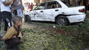 Палестинский мальчик смотрит на поврежденную машину на месте взрыва
