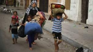 Палестинцы покидают свои дома с вещами, спасаясь от израильских авианалетов.