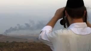 Израильтянин смотрит в бинокль в направлении сектора Газа