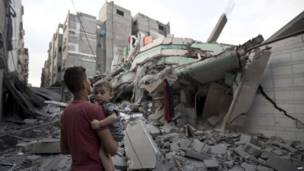 A Palestinian man carrying a child looks at the destroyed house of Hamas top leader in Gaza AFP