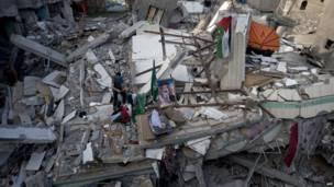 Палестинец демонстрирует флаги на руинах дома Исмаила Хании