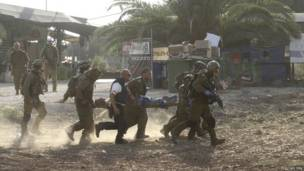 Израильские военные несут своего товарища на носилках.