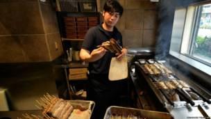 टोक्यो में एक शेफ़ ईल मछली को ग्रिल करता हुआ. यहां नेशनल ईल महोत्सव मनाया जाना है. इस दिन ईल मछली बेचने वाले रेस्त्रां रिकॉर्ड दर पर कारोबार करते हैं.