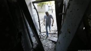 यूक्रेन की सेना की तरफ से की गई भारी बमबारी के बार केंद्रीय डोनेट्स्क में घर का जायज़ा लेता एक व्यक्ति.