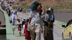 इराक-सीरिया की सीमा को पार करते विस्थापित यज़ीदी लोग