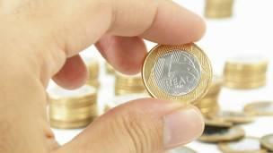 Una persona sostiene una moneda de un real entre sus dedos.