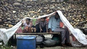 बरसात से बचने के लिए ख़ुद को प्लाटिक की एक चादर ओढ़े हुए एक परिवार.