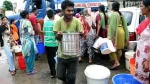 जम्मू में टैंकर से भरकर पीने का पानी ले जाता एक व्यक्ति.