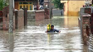 श्रीनगर में बाढ़ के पानी से होकर सुरक्षित स्थान की ओर जाता एक व्यक्ति.