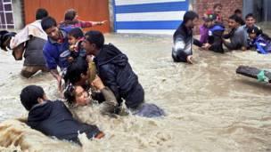 श्रीनगर में पानी के तेज़ बहाव में बचने की कोशिश करते लोग.