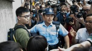 「佔領中環」運動削髮儀式會場外一名男子(左)與志願者推搡後被警員控制(9/9/2014)