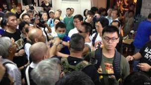 「佔領中環」運動削髮儀式會場內數名戴上手術口罩和墨鏡的示威者(中)與志願者推搡(香港電台圖片9/9/2014)