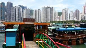 鴨脷洲島海旁掛著「往香港仔」指示牌的渡輪碼頭(前)與香港仔的住宅樓(後)