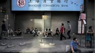 Mutane sun taru kusa da wani reshen bankin kasuwancin Shanghai yayinda ake cigaba da zanga zangar nuna goyan bayan demokradiyya a titin Nathan