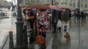 Люди на улице под зонтиками