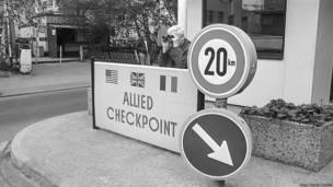 Hombre con binoculares en el Checkpoint Charlie, Berlin occidental