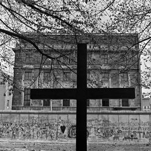 Cruz frente al muro en Berlín occidental