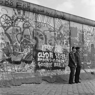 Dos soldados posan para una foto frente al muro