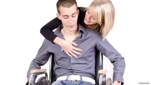 Mujer junto a un hombre en silla de ruedas.