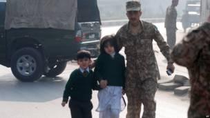 Um soldado protege duas crianças paquistanesas