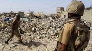 Soldados paquistaneses próximos às ruínas de uma casa no norte do país