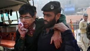 Um policial ajuda um estudante ferido
