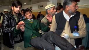 Um dos etudantes feridos no ataque é retirado do local