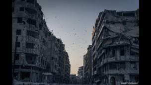सीरिया, होम्स, खालिदिया ज़िले की एक उजाड़ इमारत के ऊपर मंडराते पक्षी