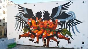 Mural del grafitero argentino JAZ, se ven hombres con cabeza águila
