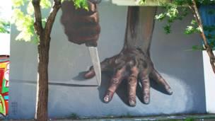 Mural del grafitero argentino JAZ, se ve una mano y un cuchillo
