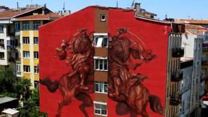 Mural del grafitero argentino JAZ, se ven dos jinetes sin cabeza