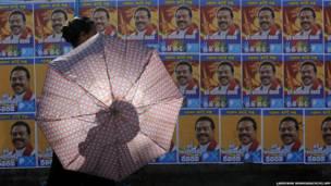श्रीलंका का राष्ट्रपति के महिंदा राजपक्षे के पोस्टर के पास से गुजरती महिला