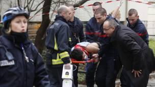 Пожарные несут на носилках одного из пострадавших